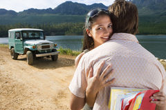 Young couple embracing near parked jeep on dirt track beside lake, woman smiling, portrait Royalty Free Stock Photos