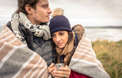 Young couple embracing outdoors under blanket in a Stock Image