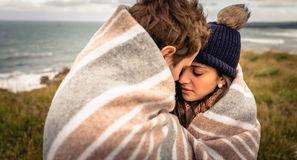 Young couple embracing outdoors under blanket in a Stock Photo