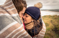Young couple embracing outdoors under blanket in a. Closeup of young beautiful couple embracing under blanket in a cold day with sea and dark cloudy sky on the Royalty Free Stock Photography