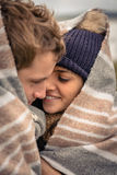 Young couple embracing outdoors under blanket in a Royalty Free Stock Photography