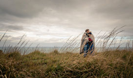 Young couple embracing outdoors under blanket in a Stock Photos