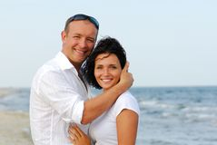 Young couple embracing by sea Stock Photos