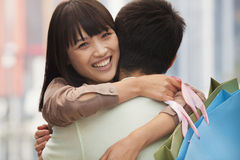 Young couple embracing with shopping bags, outdoors, Beijing Stock Image