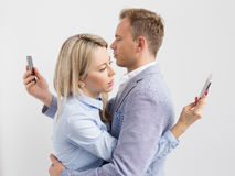 Young couple embracing and still using their mobile phones Royalty Free Stock Images