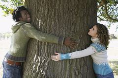 Young Couple Embracing Tree Trunk At Park. Side view of young multiethnic couple embracing tree trunk at park Stock Photo