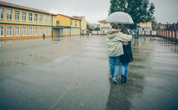Young couple embracing under umbrella walking in a Stock Images