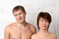 Young couple with emotions of discontent near the white wall Stock Images