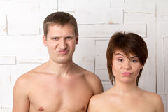 Young couple with emotions of dissatisfaction near the white wal Royalty Free Stock Images