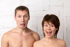 Young couple with emotions of surprise near the white wall Stock Image