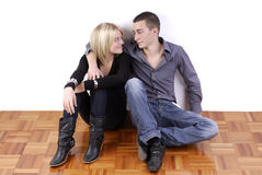 Young couple in empty room sitting on the floor Stock Photography