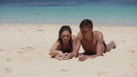 Young couple enjoy a summer beach vacation. Romantic young couple draw heart shapes in the sand.Summer beach love concept.Young man and young woman lying on sand stock video footage