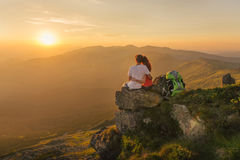 Young couple enjoy together beautiful sunset in the mountains Stock Photo