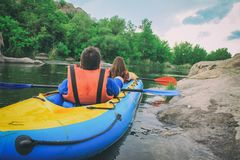 Young couple enjoy white water kayaking on the river, extreme and fun sport at tourist attraction.  Active adventure couple along. The river. Back veiw stock image
