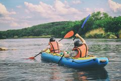 Young couple enjoy white water kayaking on the river. Extreme and fun sport at tourist attraction. Rafting on the  Pivdennyi Buh River. Active adventure couple royalty free stock images