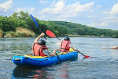 Young couple enjoy white water kayaking on the river. Extreme and fun sport at tourist attraction. Rafting on the  Pivdennyi Buh River. Active adventure couple royalty free stock photos