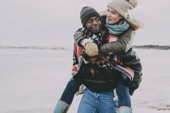 Young Couple Enjoy A Winter Beach. A young couple enjoy a winter beach as the male gives his partner a piggyback royalty free stock images