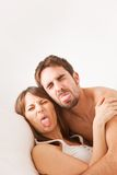 Young couple enjoying in bed and sticking out tongue Stock Photos