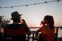 Young couple enjoying beer in a beach bar. Young couple enjoying beer and sunset in a beach bar royalty free stock photos
