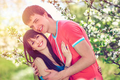 Young couple enjoying in blooming garden Royalty Free Stock Images