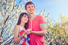 Young couple enjoying in blooming garden Stock Images