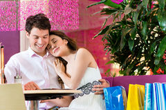 Young couple enjoying coffee after shopping Stock Photography