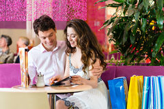 Young couple enjoying coffee after shopping Royalty Free Stock Photos