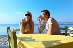 Young couple enjoying drinks at the seaside Stock Image