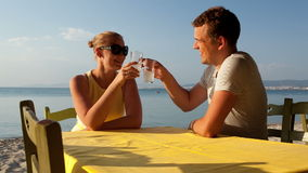 Young couple enjoying drinks at the seaside Royalty Free Stock Image
