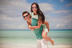 Young couple enjoying each other on sandy white Stock Photos