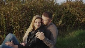 Young couple enjoying each other sitting on lawn in the autumn park stock video