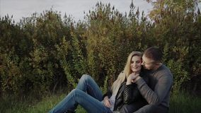Young couple enjoying each other sitting on lawn in the autumn park. HD stock video footage
