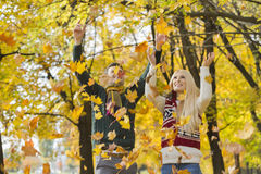 Young couple enjoying falling autumn leaves in park Royalty Free Stock Image