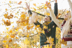 Young couple enjoying falling autumn leaves in park Stock Photography