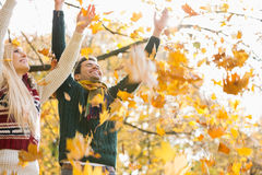 Young couple enjoying falling autumn leaves in park Stock Images