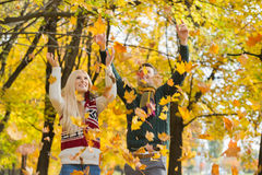 Young couple enjoying falling autumn leaves in park Royalty Free Stock Photos