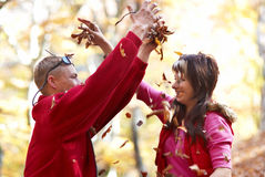 Young couple enjoying the falling leaves Stock Photos