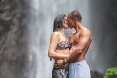 Couple at waterfall. Young couple enjoying the freshness of nature under a waterfall in the tropics Royalty Free Stock Images