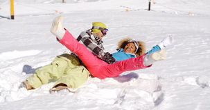 Young couple enjoying a frolic in the snow Royalty Free Stock Photography