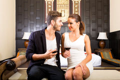 A young couple enjoying a glass of wine in a asian style hotel r Royalty Free Stock Photos