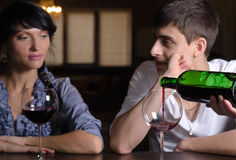 Young couple enjoying a glass of wine at the bar royalty free stock photo