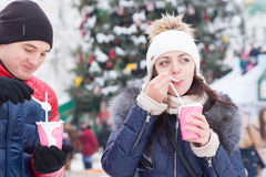 Young couple enjoying hot cappuccino in winter. As they stand outdoors at a Christmas festival or market sipping from takeaway cups stock photography