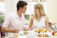 Young Couple Enjoying Hotel Breakfast. Looking at each other royalty free stock photo