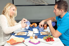 Young couple enjoying a hotel breakfast. Young couple sitting at a table enjoying a hotel breakfast with a variety of fruit, cheese, cold meat and bread on Stock Photography