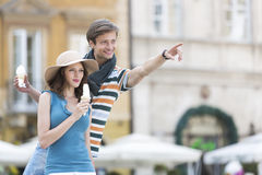 Young couple enjoying ice cream cones during vacation Stock Images