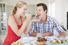 Young Couple Enjoying Meal At Home Stock Photo