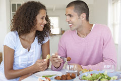 Young Couple Enjoying Meal At Home Stock Images