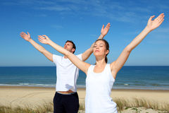 Young couple enjoying meditating on the beach Royalty Free Stock Images