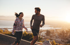 Young couple enjoying morning run. Young couple running together outdoors. Happy young men and women jogging on country road during sunrise. Two people enjoying royalty free stock photography