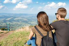 Young couple enjoying mountains landscape, sitting on hill back to camera. Young beautiful couple enjoying mountains landscape, sitting on hill back to camera Stock Image